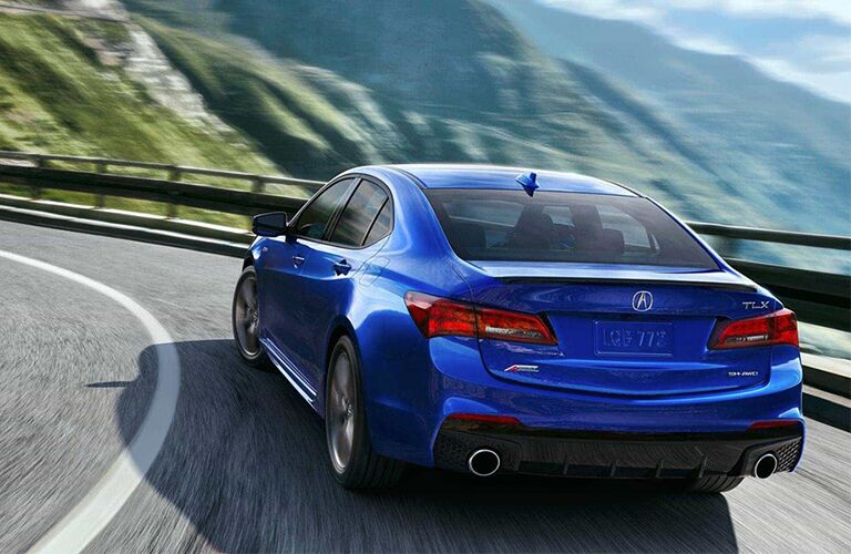 Rear view of blue 2019 Acura TLX driving on mountainous road