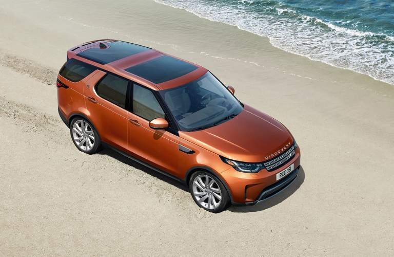 2018 Land Rover Discovery in orange color driving on the beach