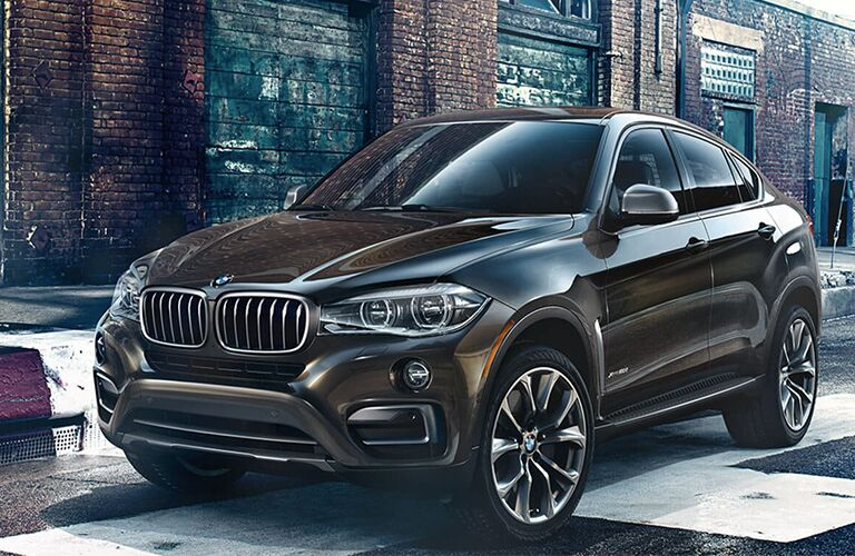 Brown 2019 BMW X6 Parked near a Brick Building