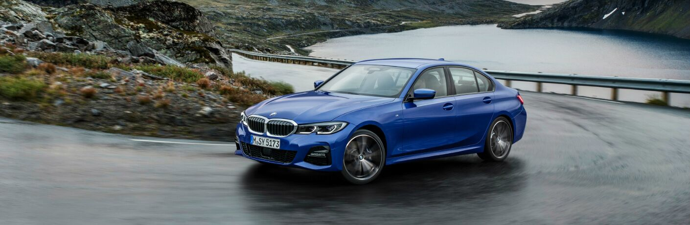 Blue 2019 BMW 3 Series Driving by a Mountain Lake