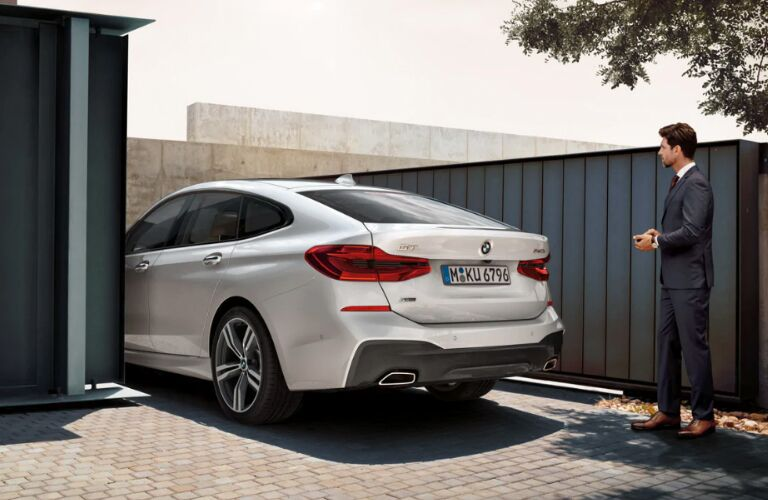 Man Standing Behind a White 2019 BMW 6 Series