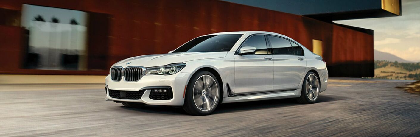 White 2019 BMW 7 Series Driving by a Long House