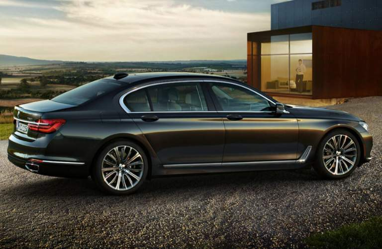 A man inside of a house looking at a 2019 BMW 7 Series