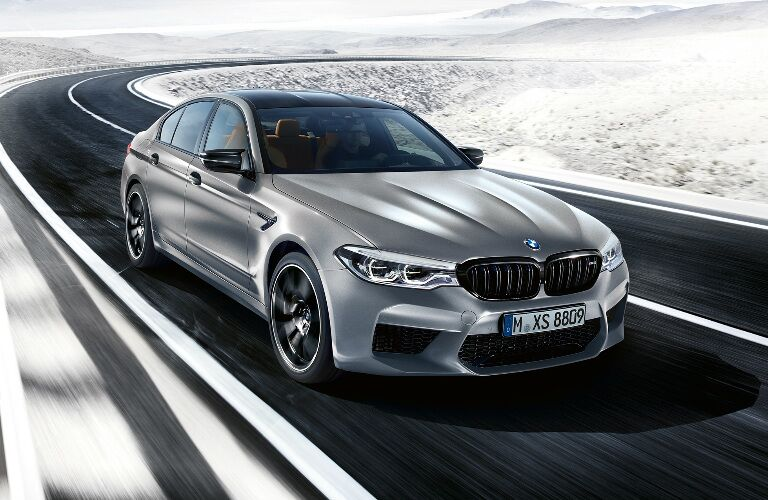Front View of Silver 2019 BMW M5 Competition Sedan Driving Through a Snowy Area