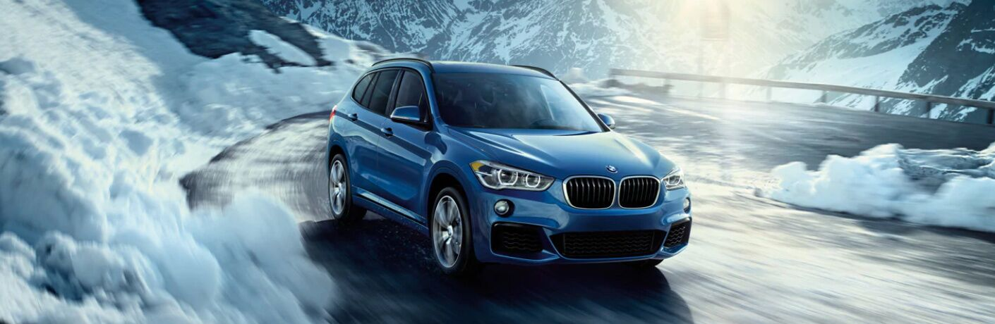 Blue 2019 BMW X1 driving on a mountainous road