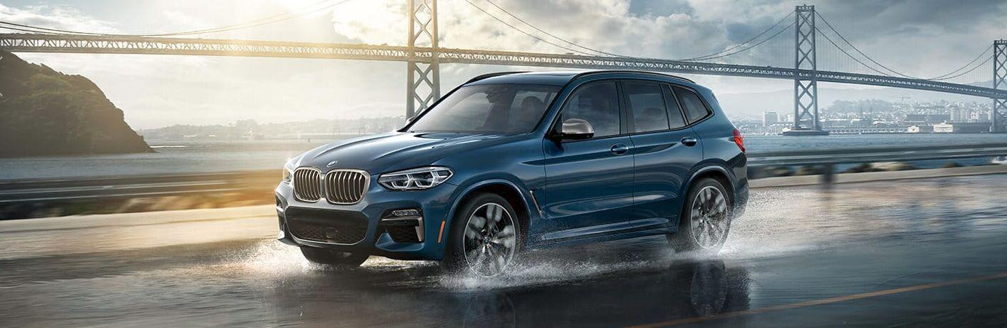 Blue 2019 BMW X3 Driving by a Bridge