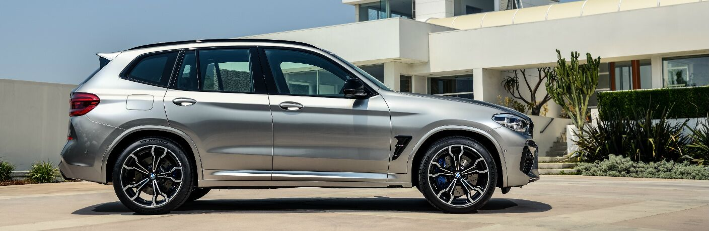 Silver 2020 BMW X3 M parked by a large white house