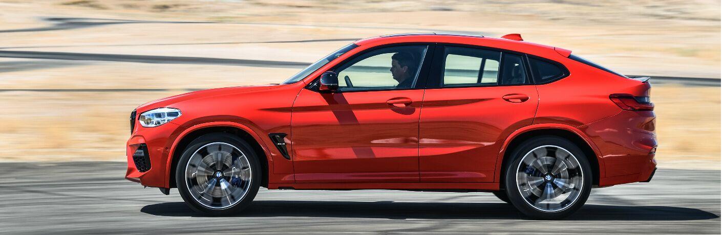 Side view of orange 2020 BMW X4 M