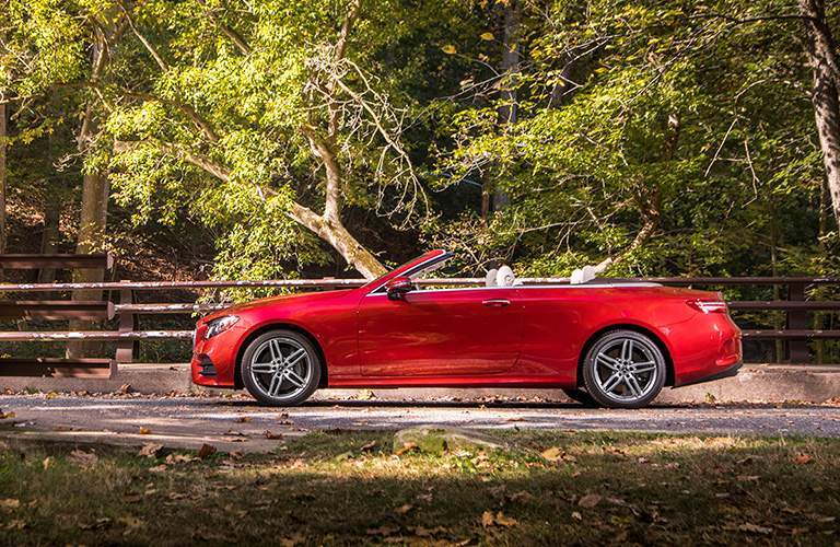 side view of a red 2018 Mercedes-Benz E-Class Cabriolet with the forest in the background