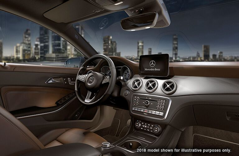 dashboard and steering wheel view in 2019 Mercedes-Benz CLA with city skyline at night in background