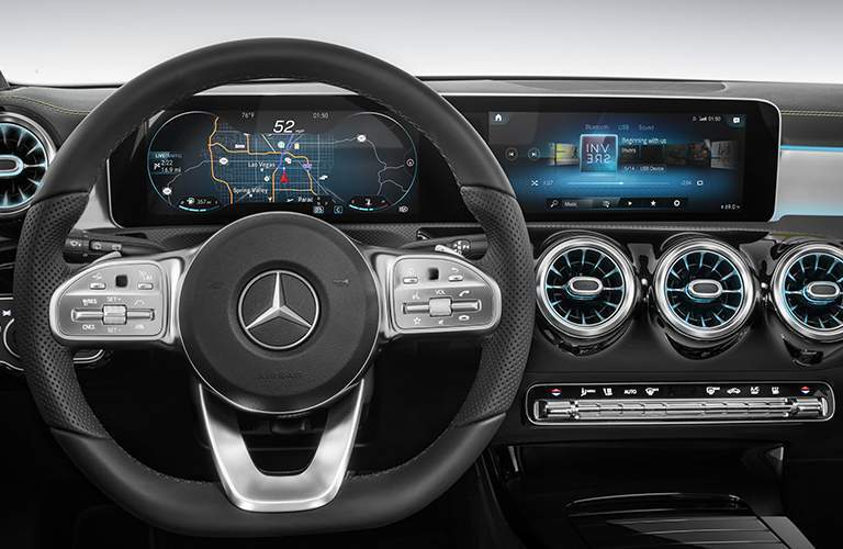 steering wheel and Mercedes-Benz User Experience Infotainment System showing some functions