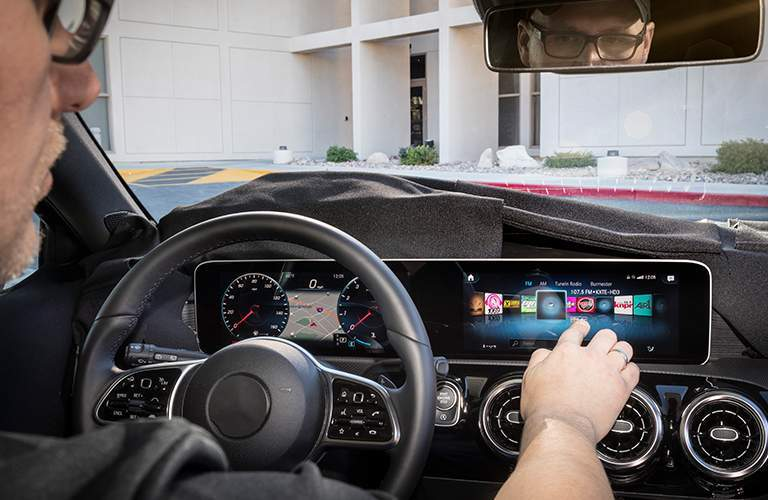 person using the infotainment features on the Mercedes-Benz User Experience Infotainment System on the new touchscreen