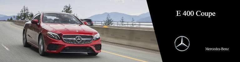 red 2018 Mercedes-Benz E-Class Coupe driving on the road, with a black label on the right