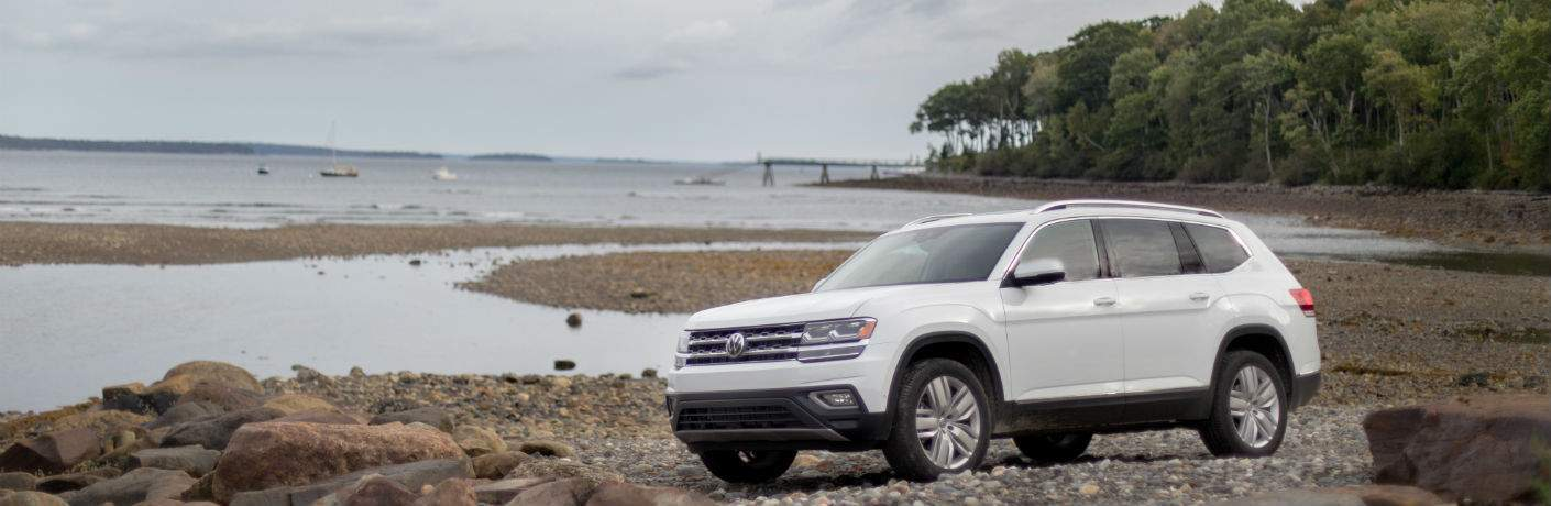 A left profile view of a white 2018 VW Atlas parked by a lake