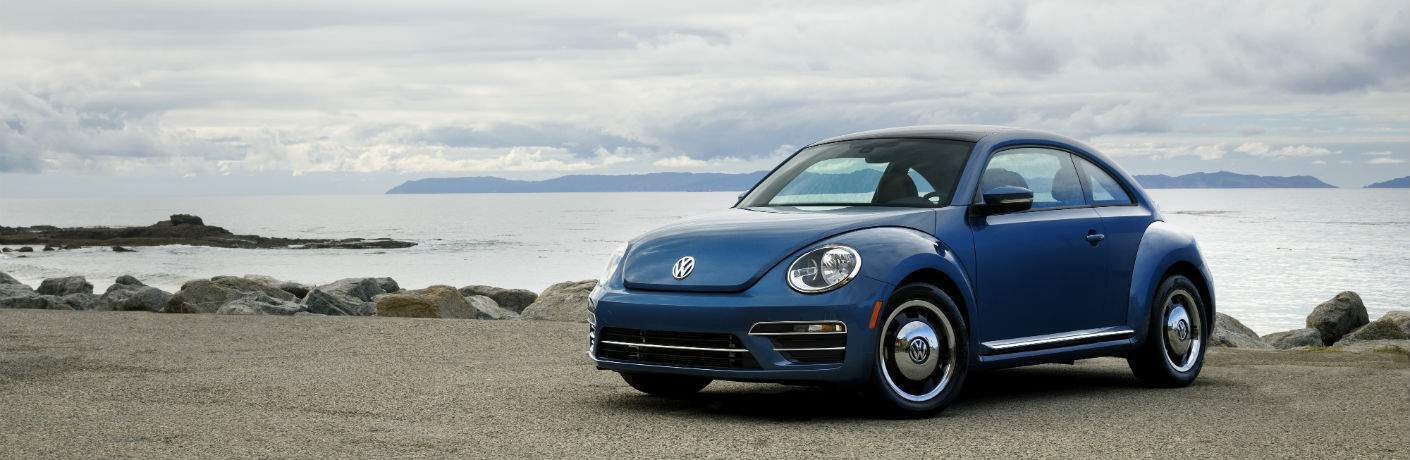 A front quarter view of the 2018 Volkswagen Beetle in front of an ocean background