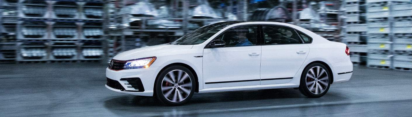 A left profile view of a white 2018 Volkswagen Passat driving through the factory