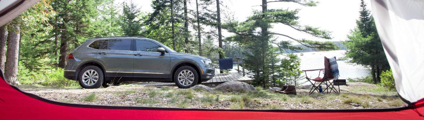 A photo of a 2018 Volkswagen Tiguan parked outside of a tent at a camp site