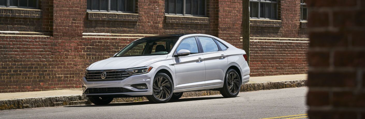 A left profile photo of the 2019 VW Jetta parked on the side of a city street.