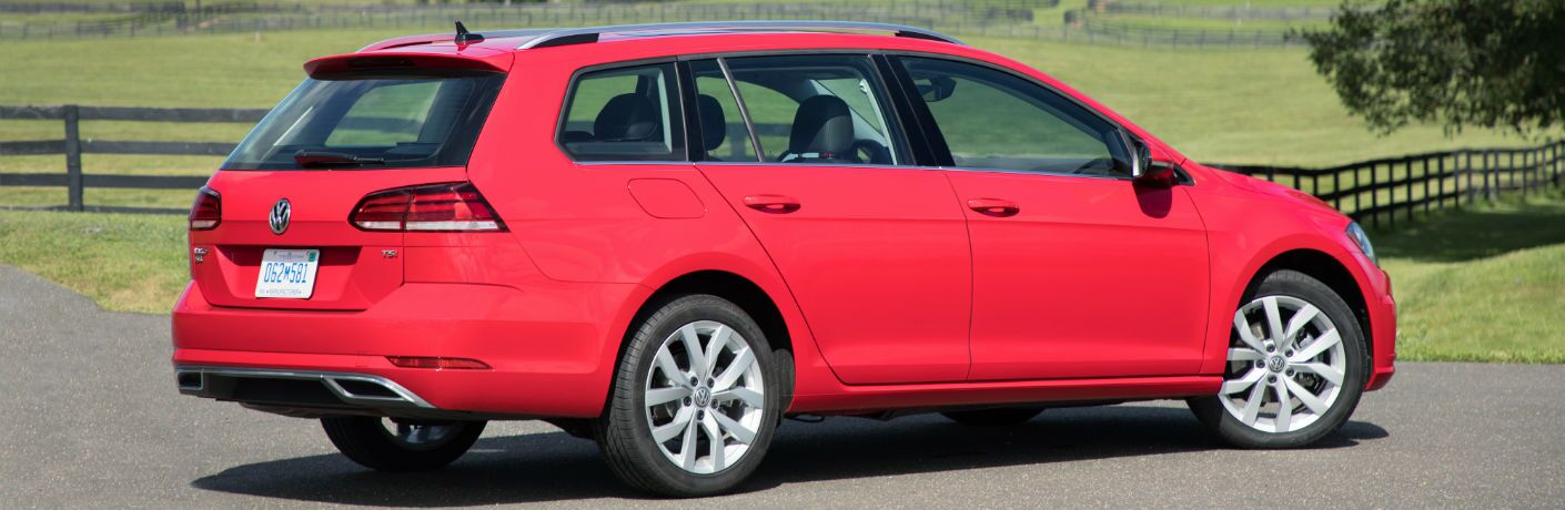 A right profile photo of the 2018 Volkswagen Golf SportWagen parked by a field.