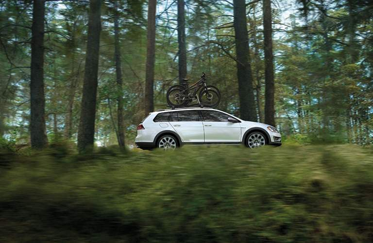 A white 2018 Volkswagen Golf Alltrack with a bike rack on the roof driving through the woods