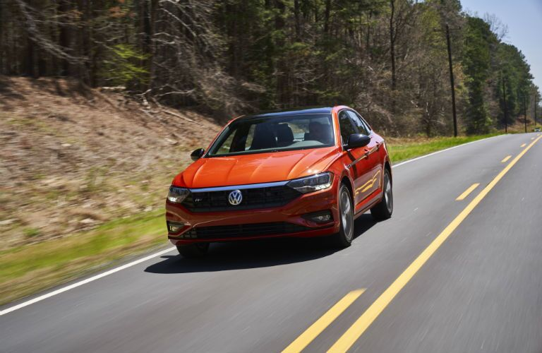 A front end photo of the 2019 VW Jetta driving on a rural road.