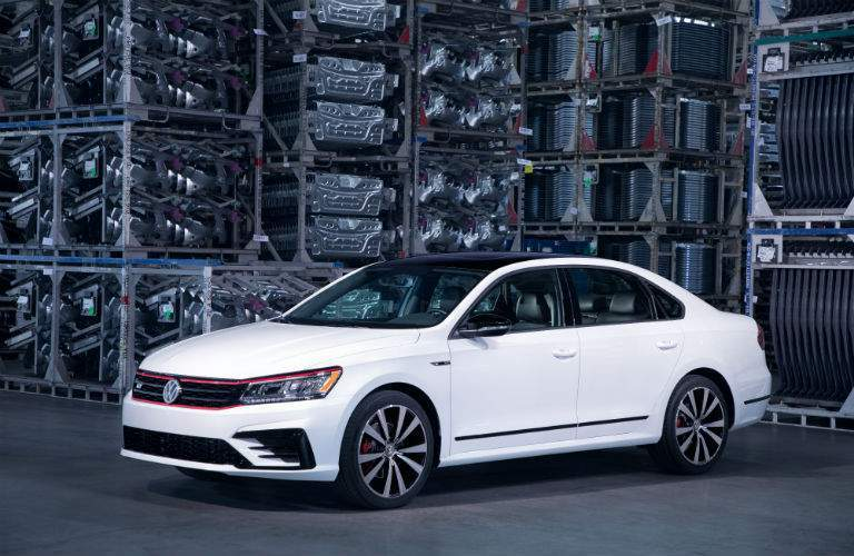 A front left quarter view of a white 2018 VW Passat parked in a factory