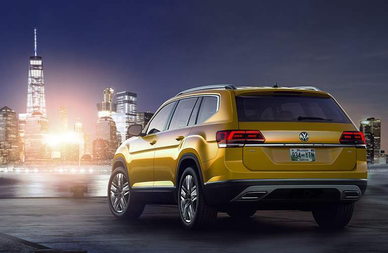 A rear left quarter view of a yellow 2018 Volkswagen Atlas in front of city skyline
