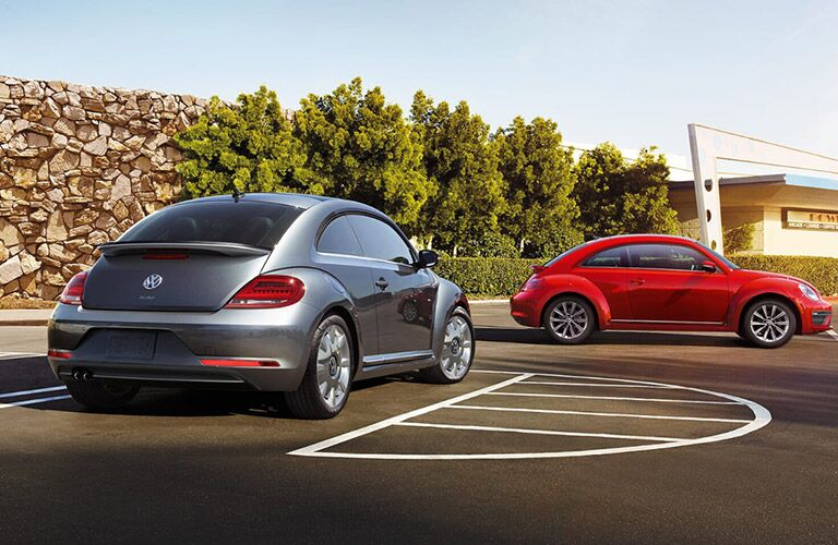 A photo of two versions of the 2018 VW Beetle in a parking lot.
