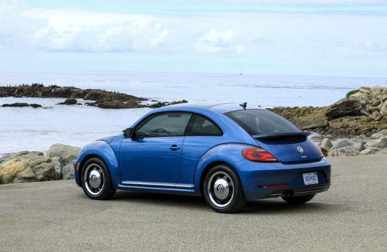 A left profile photo of a blue 2018 VW Beetle near the ocean