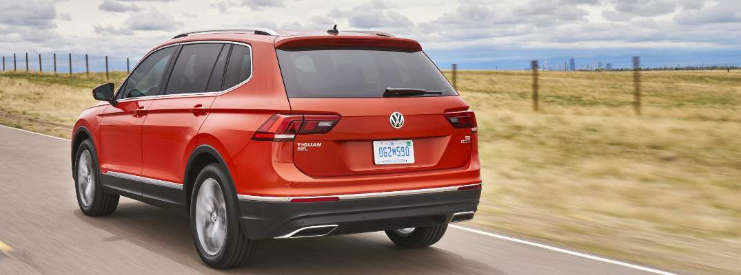 A rear quarter view of a 2018 VW Tiguan traveling down a country road