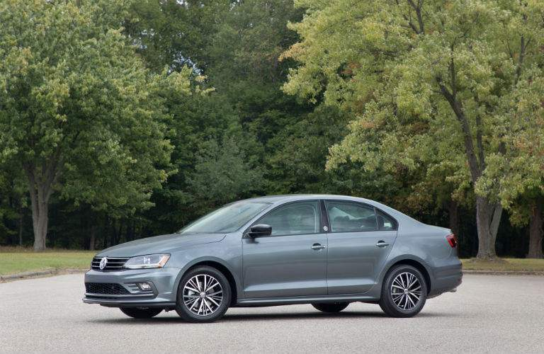 A left profile photo of a gray 2018 Volkswagen Jetta in a parking lot