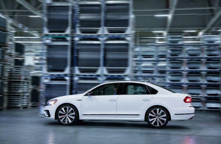 A left profile photo of the 2018 VW Passat GT driving through a factory.