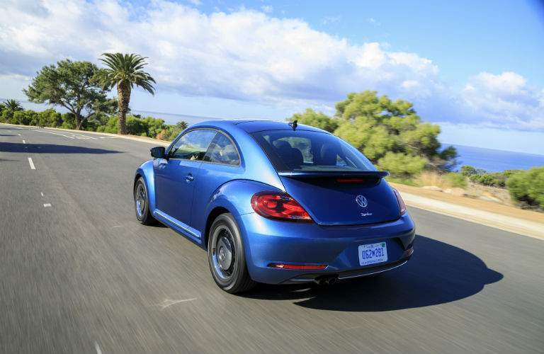 A rear left quarter view of a blue 2018 Volkswagen Beetle