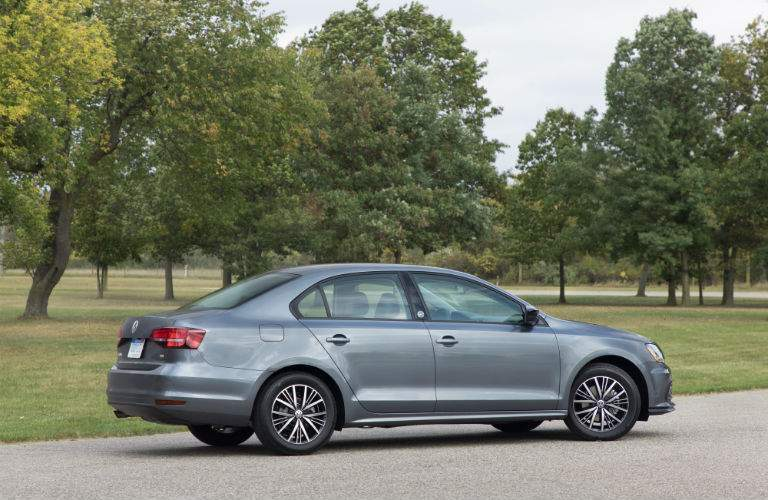 A right profile view of a gray 2018 Volkswagen Jetta in a wooded parking lot