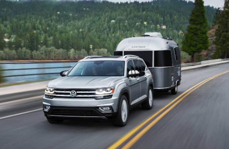A gray 2018 Volkswagen Atlas pulling a trailer down a lakeside road