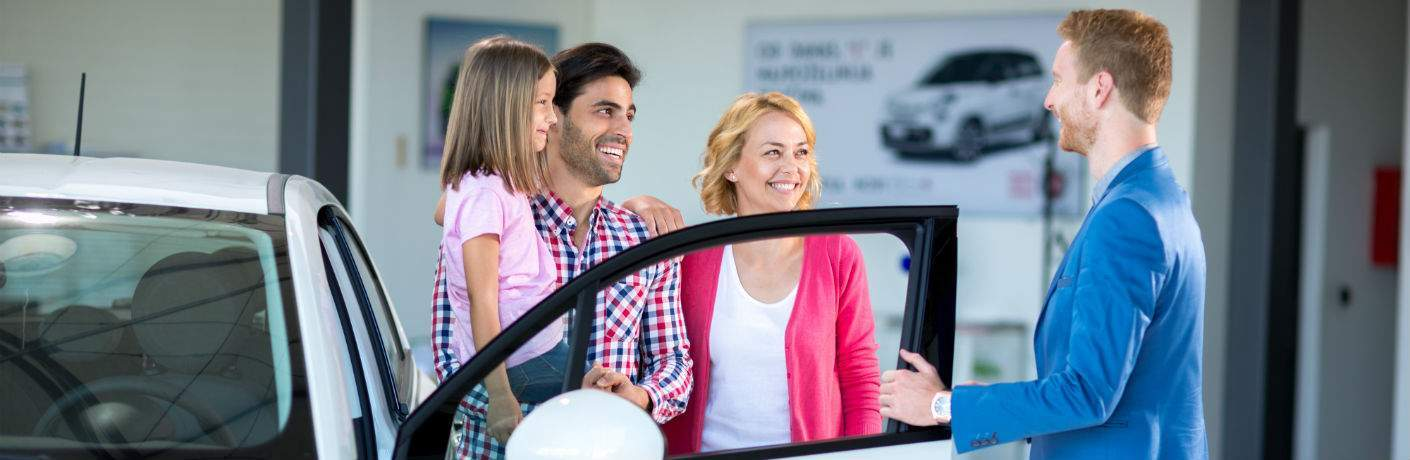 A stock photo of a car product expert helping a young family choose a new vehicle