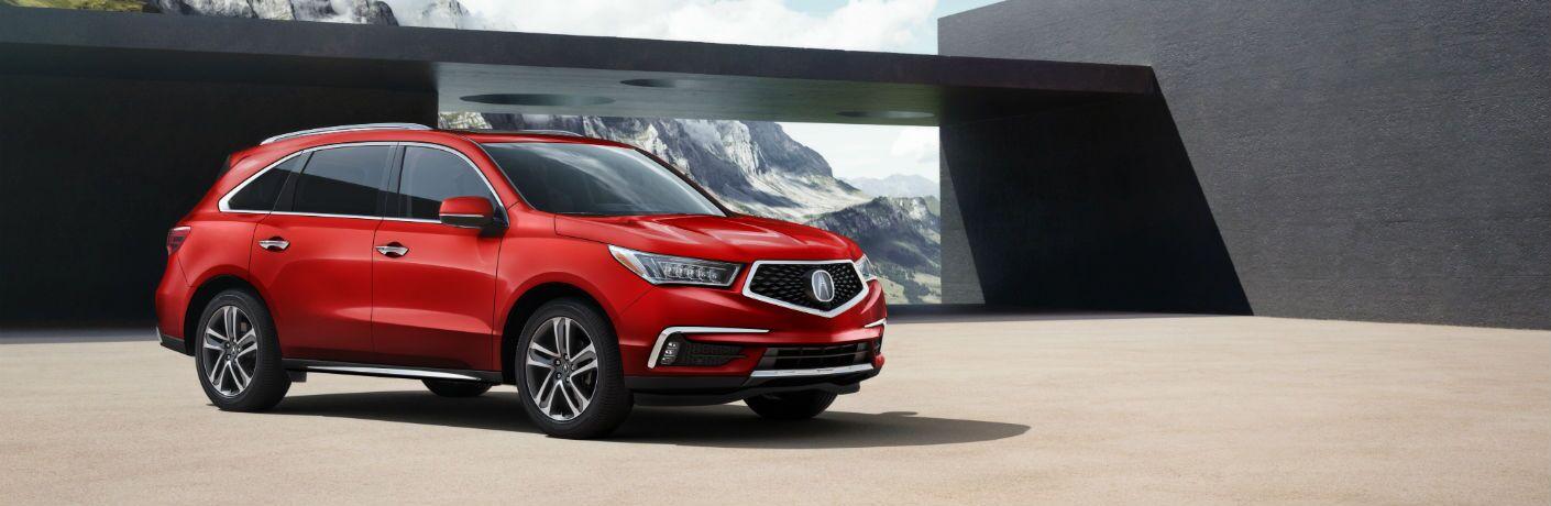 A right profile photo of a 2018 Acura MDX parked in front of a building.