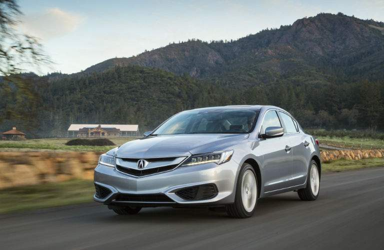 A front left quarter view of a gray 2018 Acura ILX driving over a country road