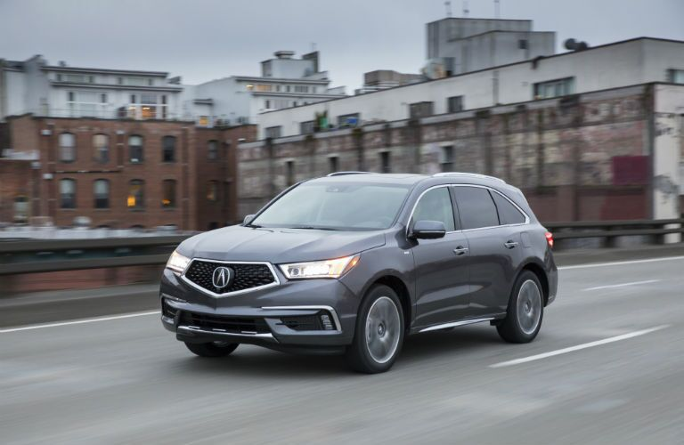 A front left quarter photo of the 2018 MDX Sport Hybrid driving through a city.
