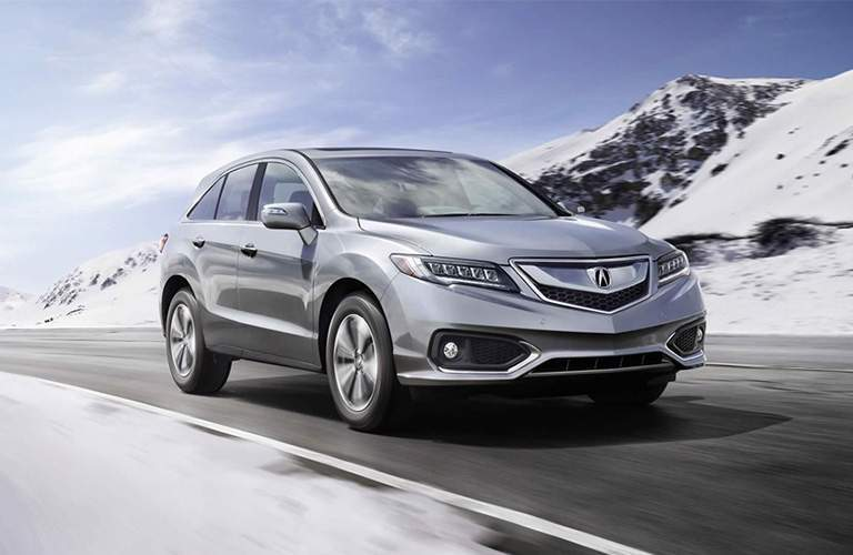 Silver 2018 Acura RDX travelling down a road with mountains on the side