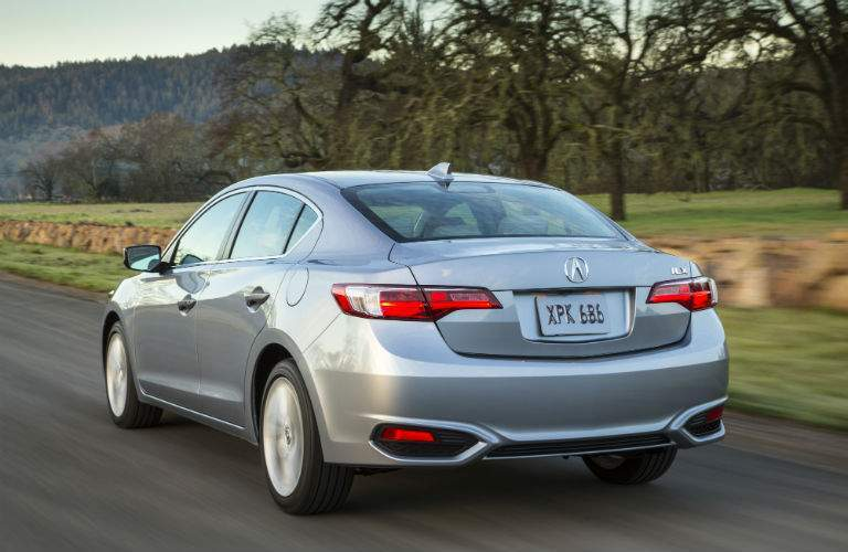 A rear quarter view of the 2018 Acura ILX driving through the country.