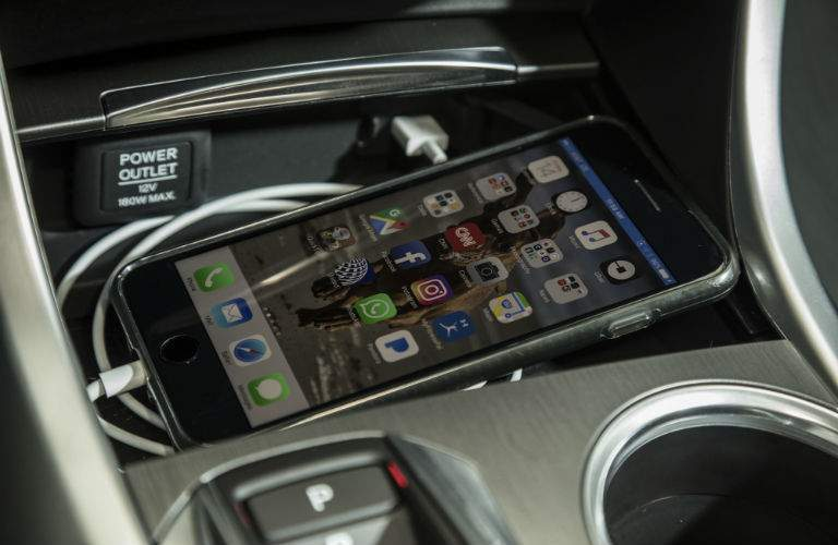 A smartphone lies in a storage tray connected via USB chord to charge inside the 2018 Acura TLX
