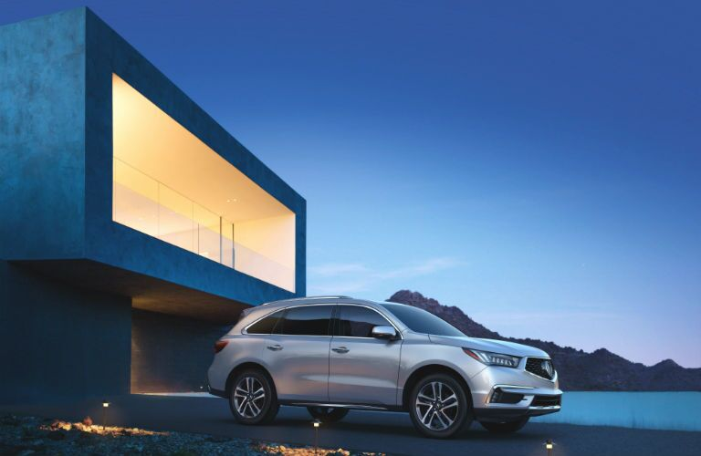 A right profile photo of the 2018 Acura MDX in front of a building.