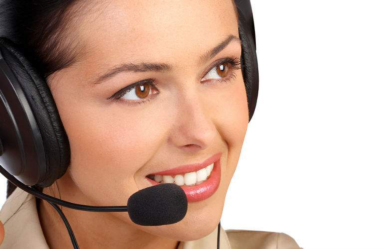 A stock photo of a woman wearing a headset representing the Acura Concierge Service