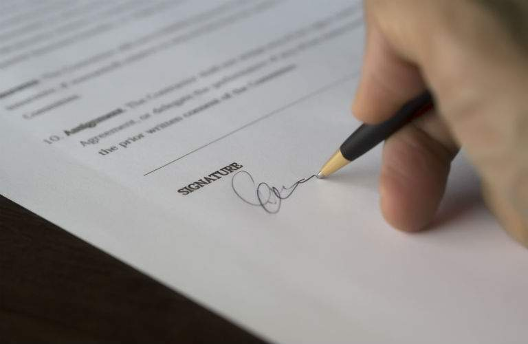 A stock photo of a person signing paper work.