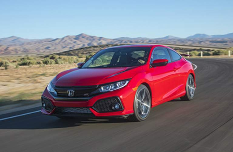 Red 2017 Honda Civic Si driving on open road