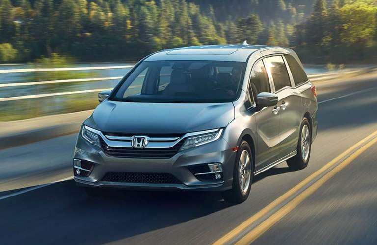silver 2018 Honda Odyssey driving near water body