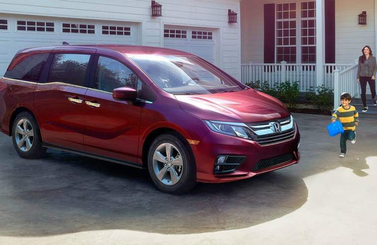 Mom and child walking towards red 2018 Honda Odyssey