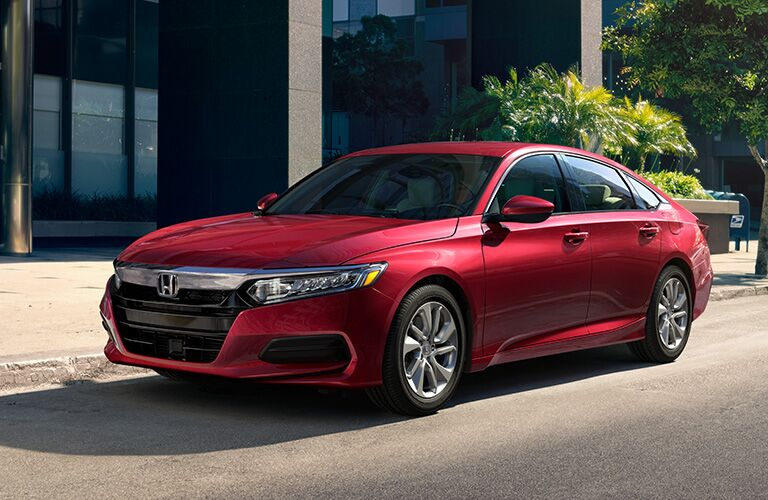 Red 2019 Honda Accord parked on the side of a road in front of a modern building.