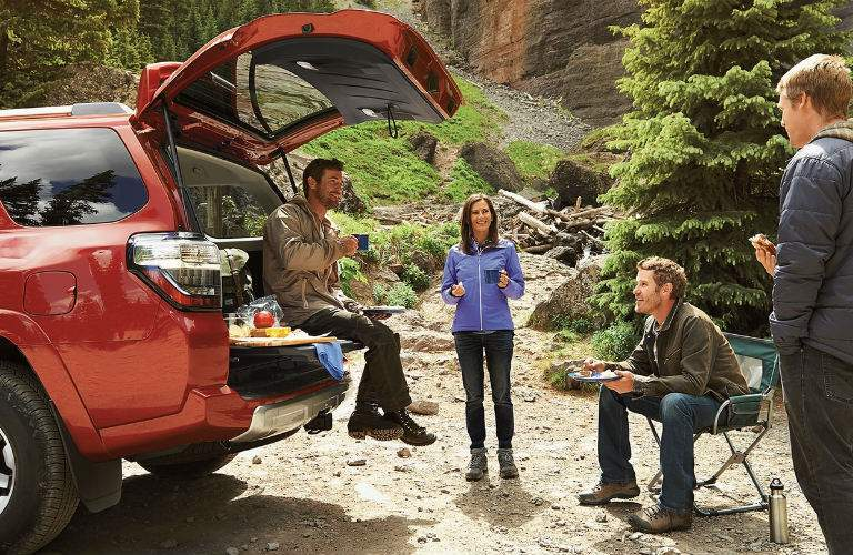 group of friends enjoying a meal by their red 2017 Toyota 4Runner